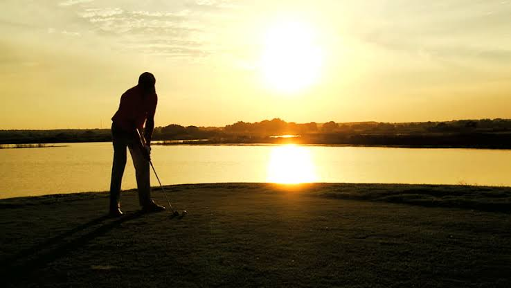 New Year Golfing Resolutions - Golfer putting with a sunset background