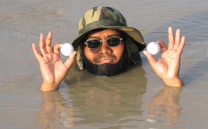 Lost income for many workers at golf clubs around Thailand. A diver collecting golf balls out of the lake poses for a photo.
