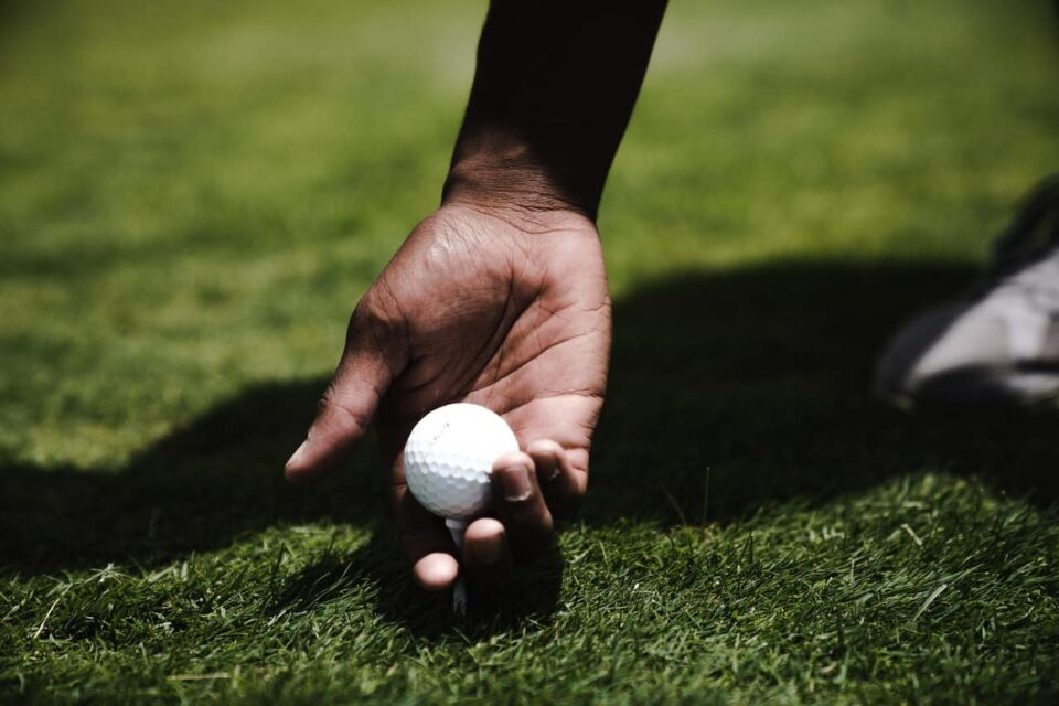 Person holding a golf ball about to hit a golf shot