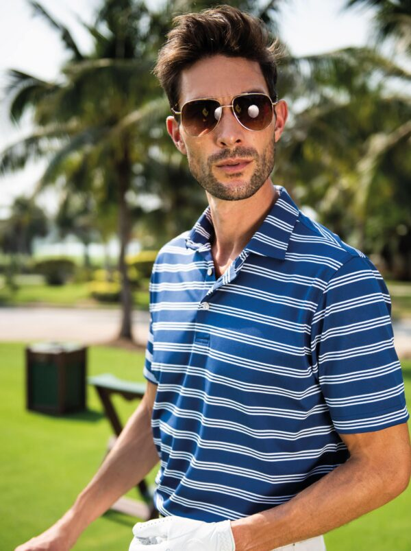 Model on golf course wearing sunglasses posing in a Fenix XCell PE blue and white striped polo shirt