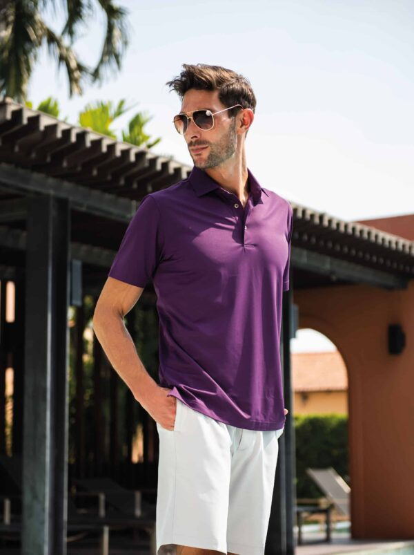 Model posing in a purple Fenix XCell PE polo shirt
