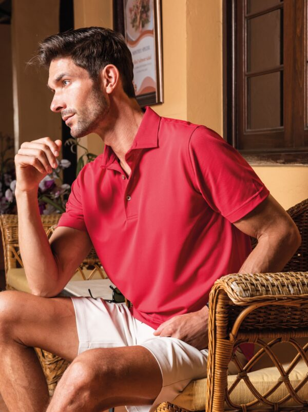 Model sitting down on a chair wearing red Fenix XCell PE polo shirt