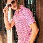 Model with glasses posing with back against a window wearing red and white striped Fenix XCell PE polo shirt