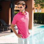 Model posing by swimming pool wearing pink ponce de leon Fenix XCell PE polo shirt