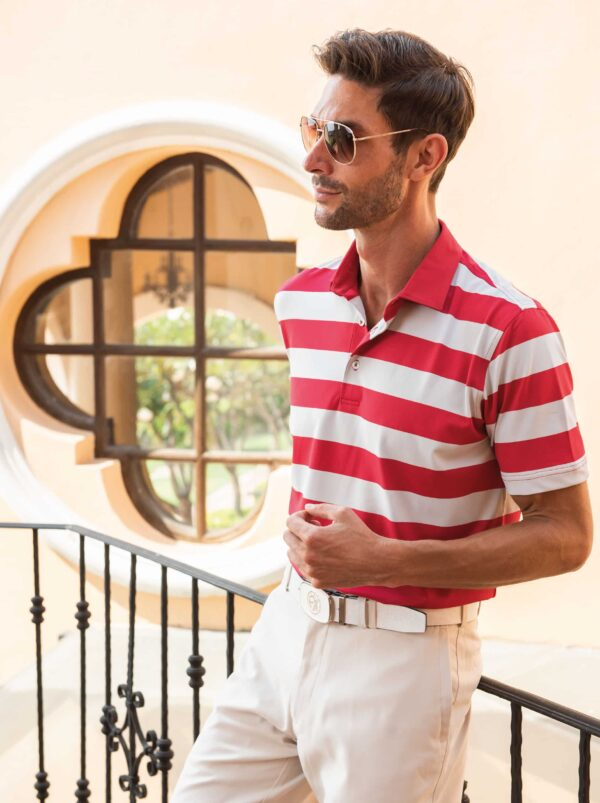 Model posing wearing red and white rugby style Fenix XCell polo shirt