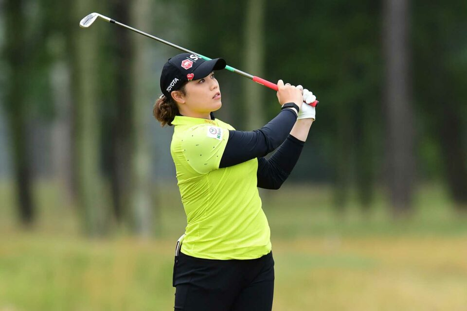 Ariya Jutanugarn hitting a golf shot wearing a yellow golf polo