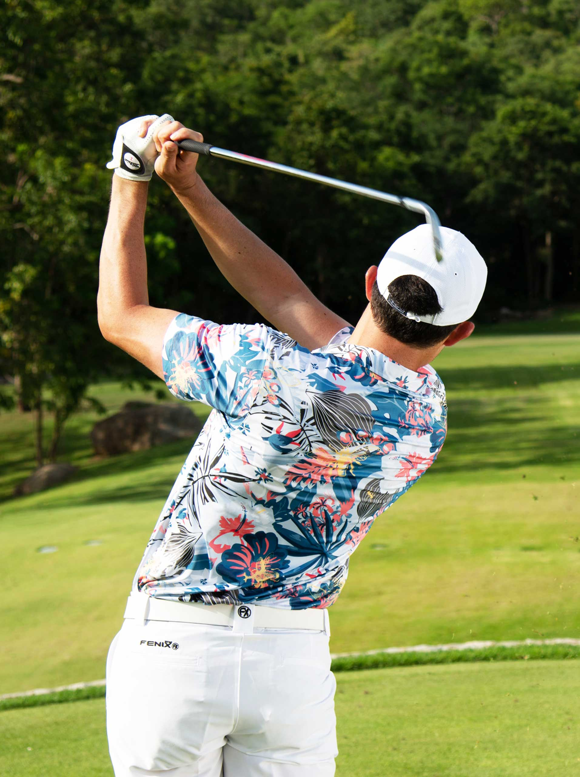 Golfer follow through wearing Fenix XCell tropical collection golf polo shirt and white Fenix XCell golf shorts