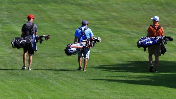 Golfers walking down the fairway carrying golf bags