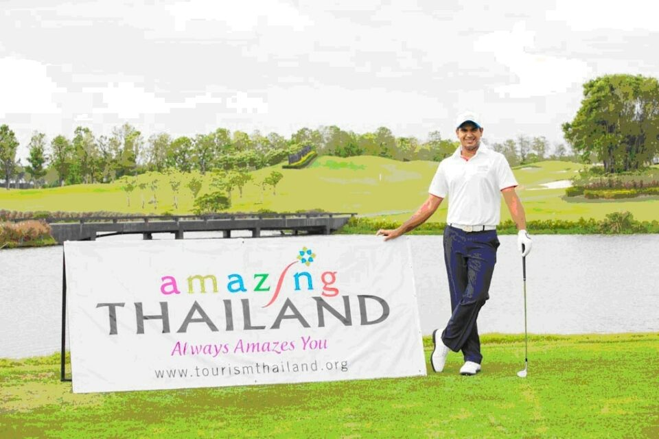Amazing Thailand sponsor board and golf standing next to it in white golf polo