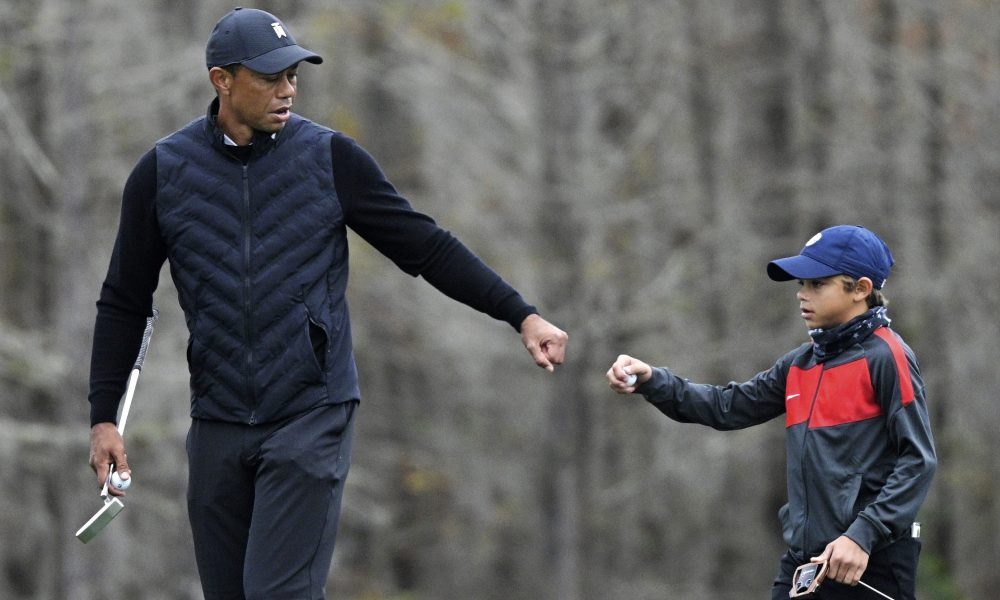 Tiger Woods giving his son Charlie Woods a first pump on the golf course
